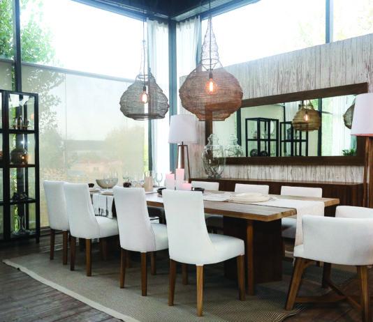 """Este espacio fue armado por una mesa de comedor """"Y"""" (llamada así por la forma de las bases que sostienen la tapa), en una medida de 3x1,20 metros. Está realizada completamente en madera maciza de petiribí, con una terminación orgánica que genera una textura rústicaen lovisual y agradable al tacto. Está acompañada por tres modelos de sillas elegidos por los clientes: Curve, Otto y, en las cabeceras, Grey, tres opciones diferentes en formología pero todas tapizadas y muy cómodas para disfrutar de las reuniones. Detrás de la mesa se encuentra el vajillero Roma, de líneas rectas, realizado también en petiribí, puertas con sistema de apertura tipo push y estantes en el interior. Por encima de éste, un espejo en sentido horizontal, con marco de madera de la misma madera. Ambos muebles acompañan el largo de la mesa. En cuanto a luminarias, sobre la mesa optan por el modelo Cap tejido, que se refleja en los espejos, y como iluminación auxiliar, la lámpara de pie Net, en petiribí con pantalla de lino. Por último, debajo de la mesa una alfombra lavable."""